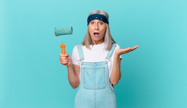 Mujer de cabello blanco de mediana edad que se siente extremadamente conmocionada y sorprendida con un rodillo pintando una pared