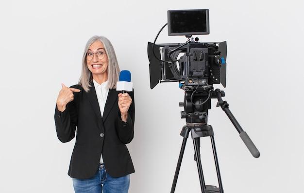 Mujer de cabello blanco de mediana edad que se siente feliz y apuntando a sí misma con un emocionado y sosteniendo un micrófono