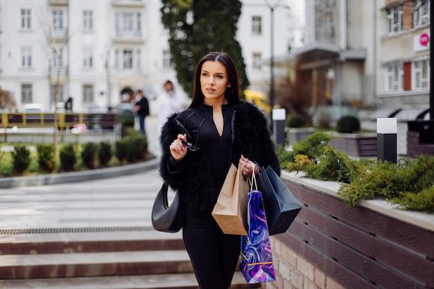Una mujer de cabello castaño vestida de negro, sostiene bolsas de compras coloridas y estampadas durante una exitosa juerga de compras. caminando afuera, ella disfruta del calor de un día.