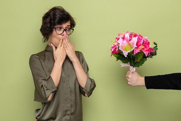 Mujer con cabello corto mirando sorprendida y feliz mientras recibe ramo de flores de su novio celebrando el día internacional de la mujer el 8 de marzo de pie sobre fondo verde