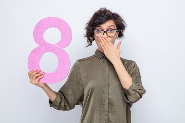 Mujer con cabello corto sosteniendo el número ocho de cartón mirando a la cámara conmocionado cubriendo la boca con la mano celebrando el día internacional de la mujer el 8 de marzo de pie sobre fondo blanco.