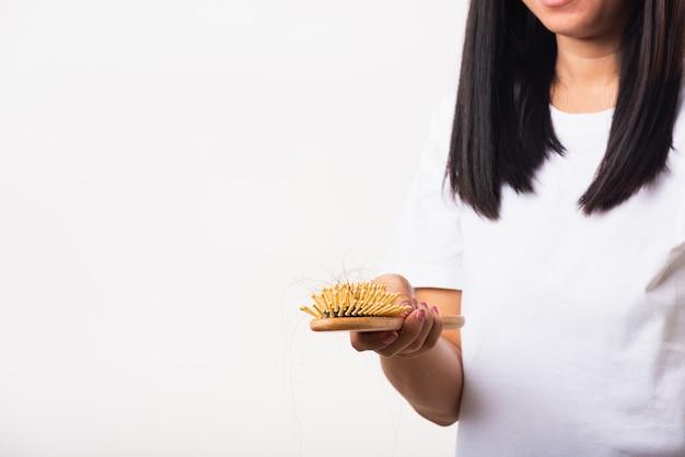 Mujer con cabello débil, muestra un cepillo para el cabello con cabello dañado de larga pérdida en el cepillo de peine en la mano