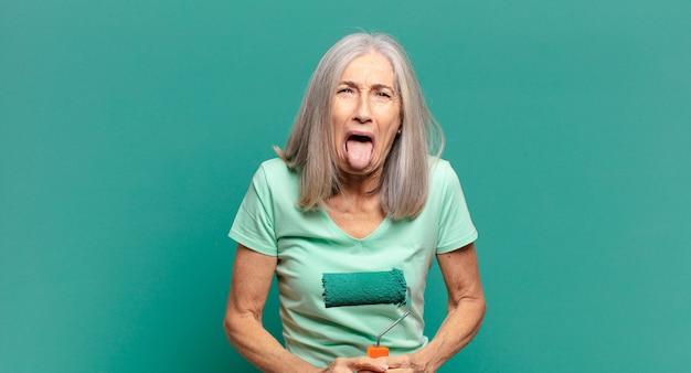 Mujer de cabello gris de mediana edad con un rodillo de pintura decorando su pared