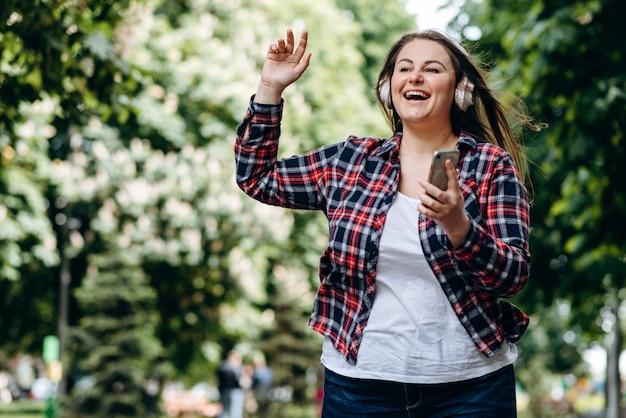 Mujer con cabello largo, con una camisa a cuadros, con auriculares, con un teléfono inteligente en sus manos al aire libre, divirtiéndose, saltando