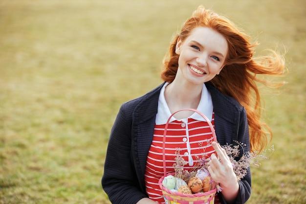 Mujer con cabello largo con cesta de picnic de pascua