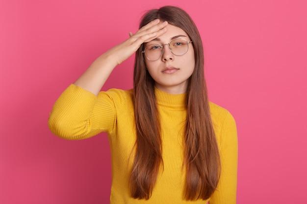 Mujer con cabello largo y hermoso que sufre de un terrible dolor de cabeza, con expresión molesta, manteniendo las manos en la frente
