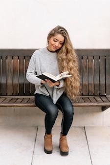 Mujer de cabello largo leyendo un libro