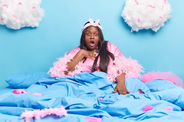 Mujer con cabello largo oscuro mira sorprendida usa diadema y bata posa en la cama debajo de la manta sorprendida al dormir reunión importante aislada en azul