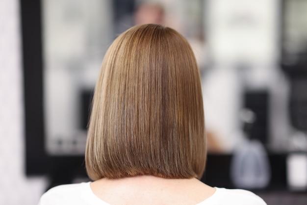 Mujer con cabello liso y uniforme sentarse en salón de belleza, vista posterior.