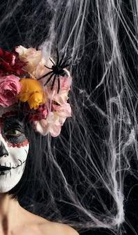 Mujer con cabello negro está vestida con una corona de rosas multicolores y maquillaje en su rostro calavera de azúcar hasta el día de los muertos