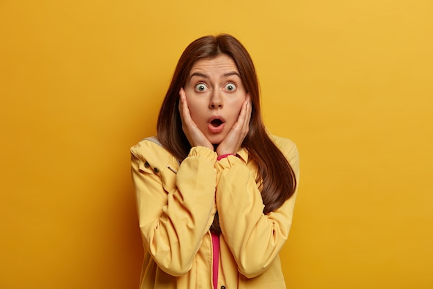 Mujer de cabello oscuro emocional asustada mira fijamente con ojos saltones, mantiene la boca abierta, aprendió algo aterrador, usa chaqueta, aislada en la pared amarilla. concepto de reacción humana