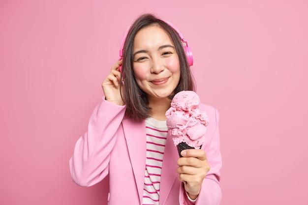 Mujer con cabello oscuro escucha música a través de auriculares vestida con ropa de moda come deliciosas poses de helado de cono