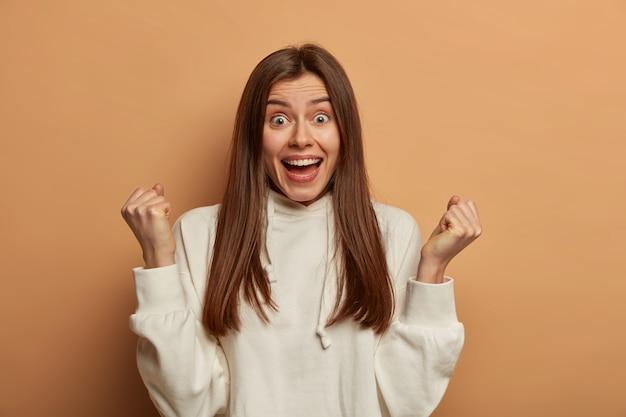 La mujer de cabello oscuro excesiva tiene una mirada muy feliz, aprieta los puños con alegría, se regocija por la victoria, abre la boca, tiene una expresión divertida, usa una sudadera con capucha informal