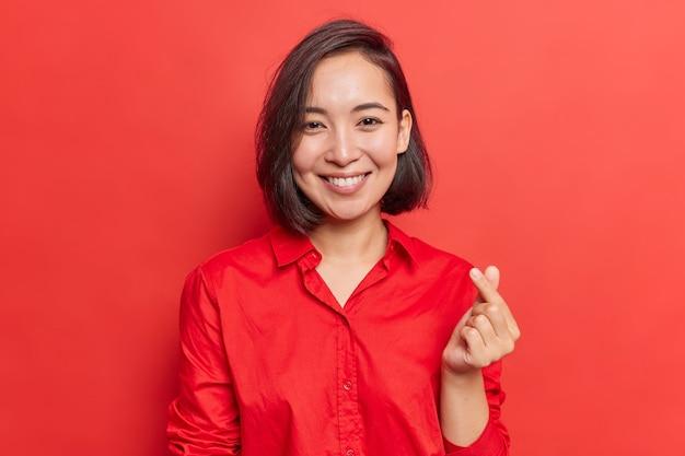 Mujer con cabello oscuro hace mini gesto de corazón símbolo coreano del amor expresa simpatía vestida con camisa roja en un tono con