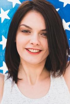 Mujer con cabello oscuro mirando a cámara y sonriendo