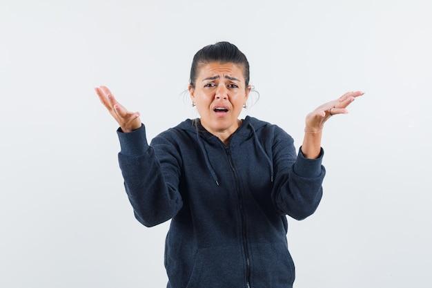 Mujer de cabello oscuro que muestra un gesto de impotencia en la chaqueta y parece pobre. vista frontal.