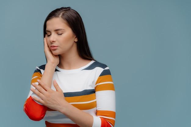 Mujer de cabello oscuro toca mejilla, sufre de dolor de muelas