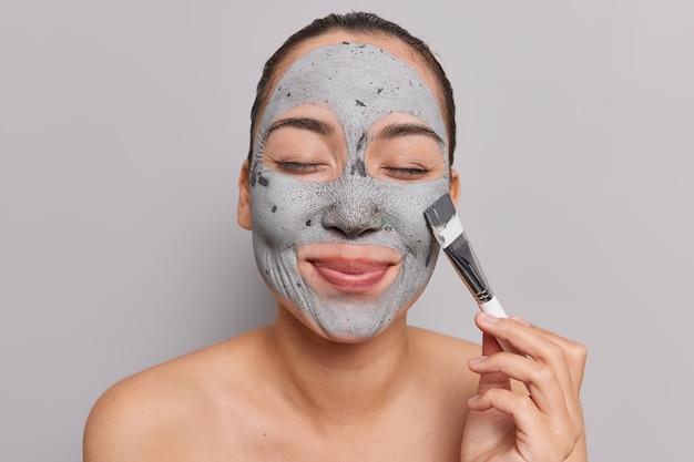 Mujer con cabello peinado mantiene los ojos cerrados aplica mascarilla de arcilla en la cara sostiene un cepillo cosmético cuida el cutis se encuentra sin camisa interior en gris