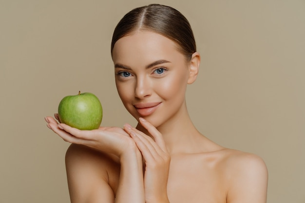 Mujer con cabello peinado tiene manzana verde fresca utiliza cosmética natural