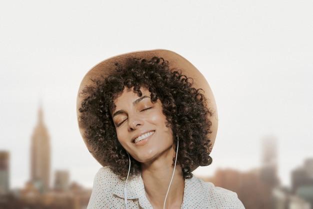 Mujer con cabello rizado con auriculares remezclados multimedia con vistas a la ciudad