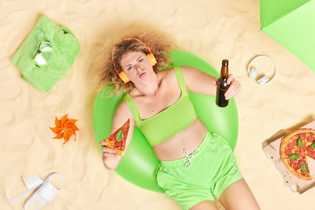 Mujer con cabello rizado come pizza y bebe cerveza escucha música a través de auriculares usa top verde y pantalones cortos se encuentra en poses de natación infladas en la playa tiene mal humor