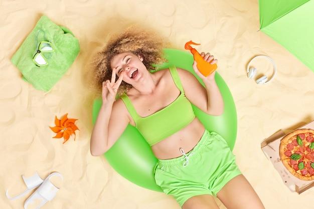 Mujer con cabello rizado se encuentra en un anillo de natación inflable verde sostiene una botella de crema solar hace un gesto de paz se divierte en la playa come pizza diferentes artículos alrededor disfruta de un buen descanso de verano