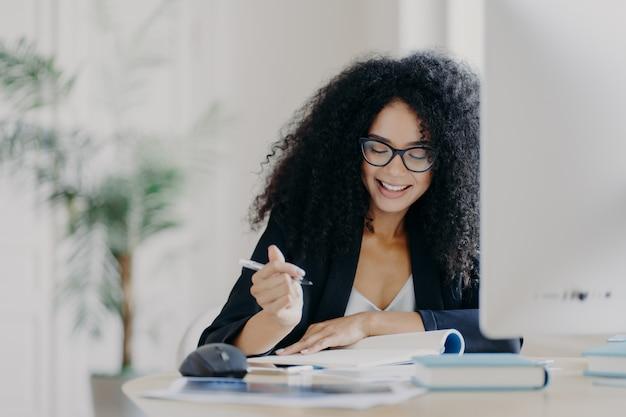 La mujer de cabello rizado escribe alguna información, sostiene la pluma, sonríe y usa lentes ópticos