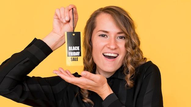 Mujer con cabello rizado con etiqueta de ventas de viernes negro vista frontal