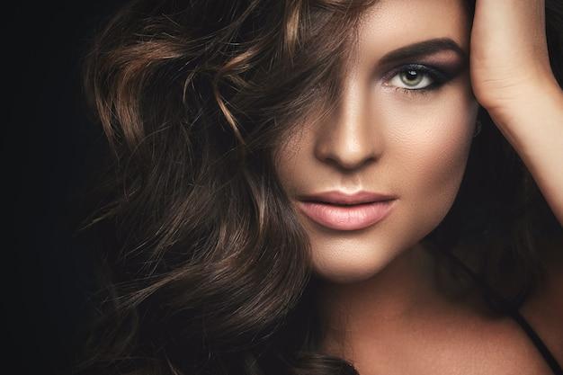 Mujer con cabello rizado y hermoso maquillaje