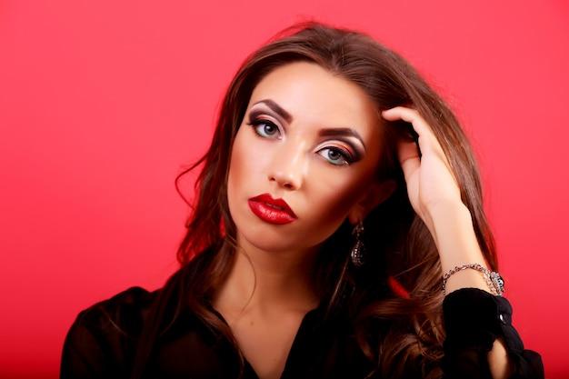 Mujer con cabello rizado oscuro que fluye y piel perfecta en rojo