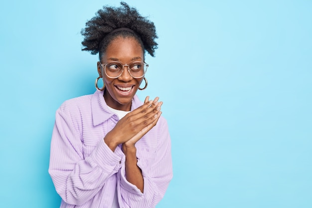 Mujer con cabello rizado sonríe ampliamente mantiene las palmas juntas juntas mira hacia otro lado planes algo usa gafas transparentes y camisa púrpura aislada en la pared azul