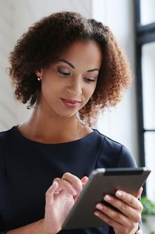 Mujer con cabello rizado usando una tableta