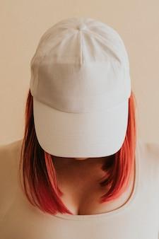 Mujer de cabello rosado fresco con una maqueta de gorra blanca