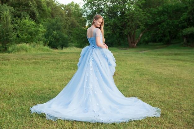 Mujer con cabello rubio en un hermoso vestido azul con mangas largas al aire libre