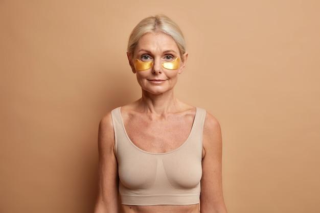 Mujer con cabello rubio peinado usa parches dorados debajo de los ojos