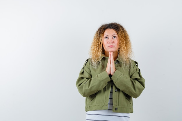 Mujer con cabello rubio rizado en chaqueta verde manteniendo las manos juntas mientras reza y mira esperanzada, vista frontal.