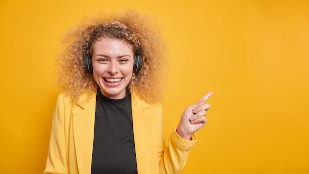 Mujer con cabello rubio rizado sonríe agradablemente indica en el espacio de copia en blanco escucha música a través de auriculares chaqueta formal