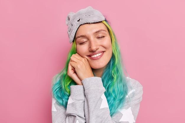 Mujer con cabello teñido toma la siesta sonríe suavemente mantiene los ojos cerrados imagina que algo tiene un buen sueño saludable usa pijama y antifaz posa en rosa