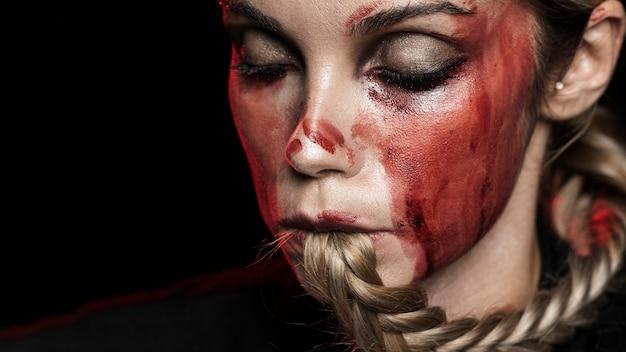 Mujer con cabello trenzado y maquillaje ensangrentado