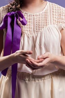 Mujer con cabello trenzado sosteniendo sus manos juntas