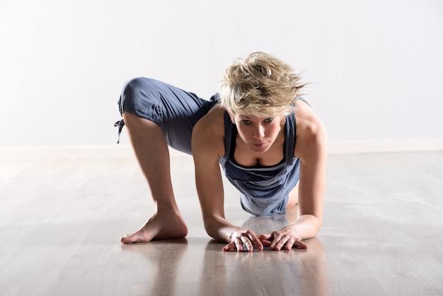 Mujer con la cabeza hacia adelante estirando una pierna