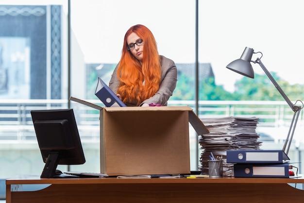 Mujer cabeza roja mudarse a la nueva oficina de embalaje sus pertenencias
