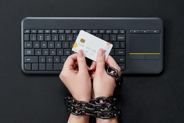 Mujer con cadena de metal con tarjeta de crédito sobre el teclado