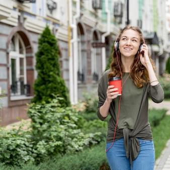 Mujer con café y auriculares.