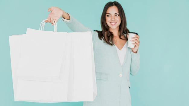 Mujer con café y bolsas de compras sobre un fondo azul.