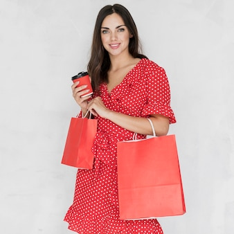 Mujer con café y bolsas de compras sonriendo a la cámara
