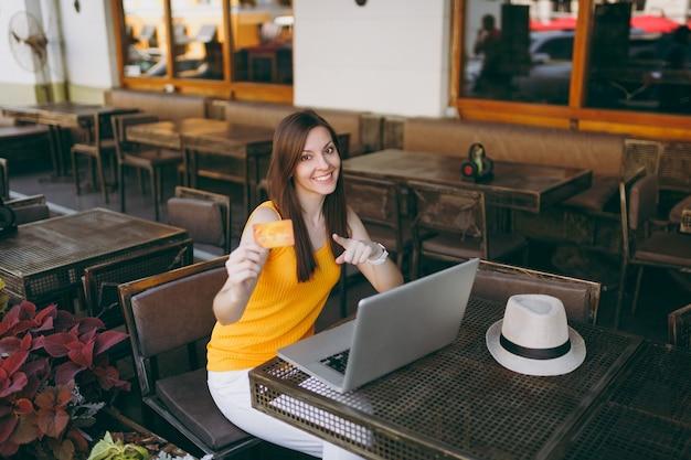 Mujer en el café de la cafetería de la calle al aire libre sentado en la mesa con un moderno ordenador portátil, tiene en la mano tarjeta de crédito bancaria