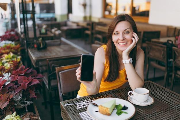 Mujer en el café de la cafetería de la calle al aire libre sentado en la mesa con una taza de té, pastel, mantenga en la mano el teléfono móvil con pantalla vacía en blanco