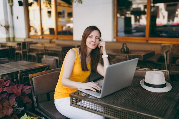 Mujer en el café de la cafetería de la calle al aire libre sentado en la mesa trabajando en una computadora portátil moderna, relajándose en el restaurante durante el tiempo libre
