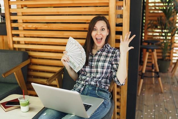 Mujer en el café de la cafetería de la calle al aire libre sentado con un moderno ordenador portátil, mantenga en la mano un montón de billetes de dólares, dinero en efectivo